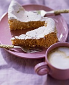 Almond cake with icing sugar on plate; coffee