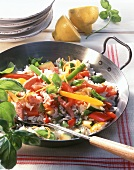 Vegetable paella with diced ham and basil