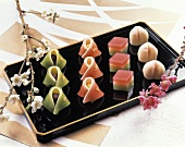 Japanese sweets on black platter; flowers