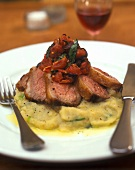 Lamb fillet on artichoke puree with tomatoes and olives