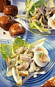 Herring salad with potatoes, apples & egg; bread roll