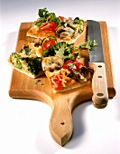 Colourful vegetable pizza in pieces on chopping board