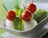 Tomato & mozzarella on cocktail sticks with fresh basil