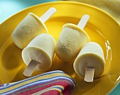 Pineapple and ginger ice cream on stick on yellow plate