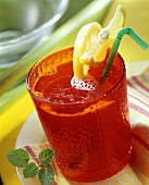 Fruit juice punch in red glass with lemon wedges