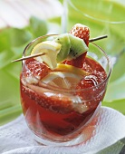 Strawberry and kiwi punch with lemon wedges in glass