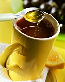Grape punch with honey in yellow cup
