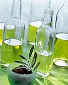 Various types of olive oil in bottles; black olives
