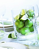 Limes in large glass container on laid table