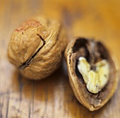 Whole and half walnut on wooden background