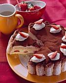 Tiramisu cake with strawberries and cream, a piece cut