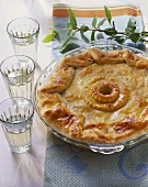 Alsatian wine-grower's pie in glass dish; white wine glasses
