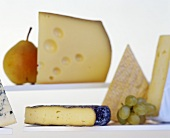 Various types of cheese with pear and grapes
