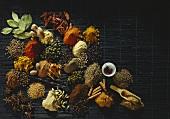 Verschiedene exotische Gewürze auf schwarzer Bambusmatte
