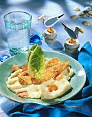 Breaded fish on mashed potato with carrot flowers