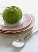 Kafir lime on pile of plates; spoon with sugar