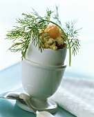 Scrambled egg with shrimps and dill in egg shell in eggcup