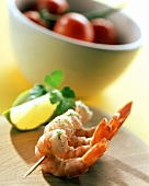 Cooked shrimps on cocktail sticks; lemon; tomatoes