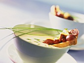 Cheese soup with fruit slices and chives