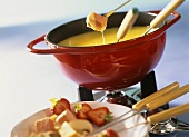 Cheese fondue with ham and strawberries in fondue pot
