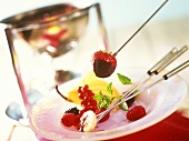 Schokoladenfondue mit Früchten auf Fonduegabeln