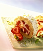 Strawberry roulade with icing sugar and chopped pistachios