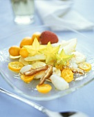 Exotic fruit salad with maple syrup and coconut flakes
