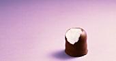 Chocolate marshmallow on mauve background (a bite taken)