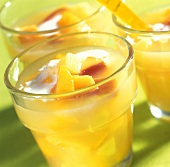 Yellow fruit compote with cream in glasses for summer party