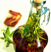 Home-made tomato and herb oil in bottle