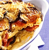 Macaroni and sausage bake with aubergines in baking dish