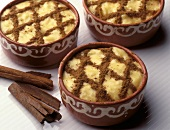 Portuguese rice dessert with cinnamon in terracotta bowls
