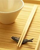 Chopsticks, fish decoration & white bowl on wooden background