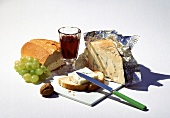 Still life with gorgonzola, bread, red wine, grapes and nut