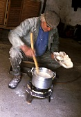 Corsican farmer cooking polenta on small gas stove