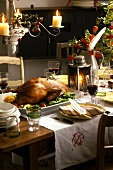 Laid table with roast Martinmas goose and red wine