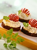 Pumpernickel with potato and herb spread and radishes
