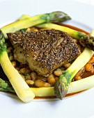 Fried sea bass on beans and green asparagus