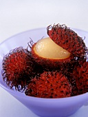Several rambutans, one half peeled