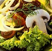 Salad ingredients: salad leaves, mushrooms, onions, tomatoes
