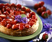 Strawberry tart in puff pastry with purple flowers