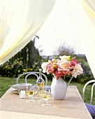 Table in open air with wine, candle and peonies