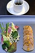 Sliced swordfish fillet with salad garnish; sauce