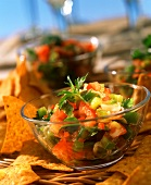 Raw tomato salsa with peppers in glass dish; tortilla chips