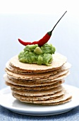 Avocado dip with chili pepper on poppy seed crackers