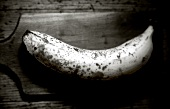 Over-ripe banana on wooden chopping board