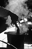 Chef throwing lobster into steaming pan