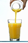Pouring orange juice from a bottle into a glass