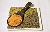 Red, brown and green lentils in bowl and spoon