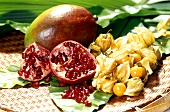 Mango, halved pomegranate and physalis
